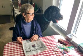 Helen MacLeod and her dog Bailey enjoy the view outside her kitchen window, like they usually do every morning, with him perched behind her on the seat while MacLeod reads the paper. Thanks to ElderDog CBRM, MacLeod, 75, is able to get help walk Bailey and she is grateful for the free services. NICOLE SULLIVAN/CAPE BRETON POST