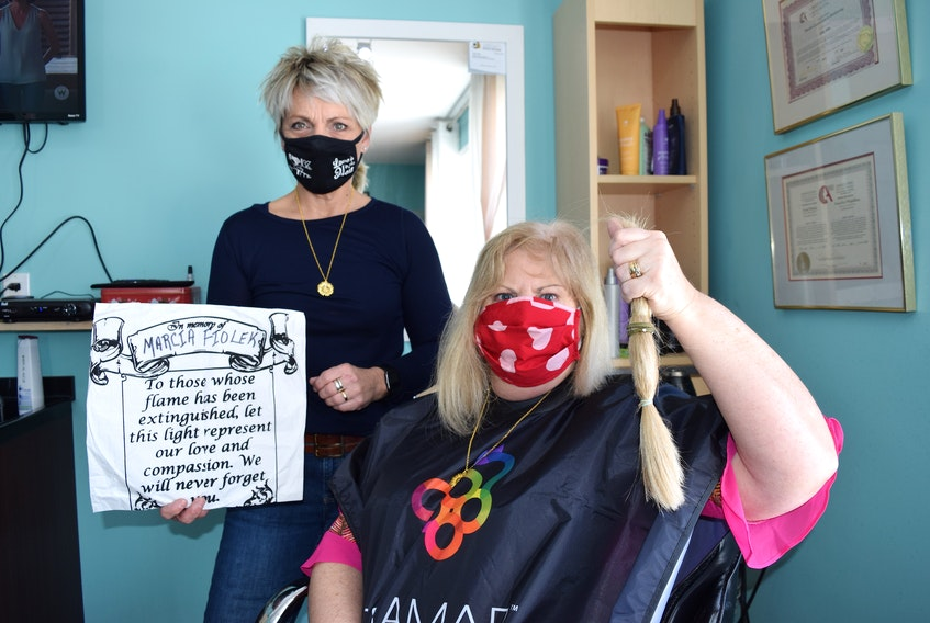 Janine Fiolek of Dominion holds up a year's worth of hair growth which was cut off by hair salon owner Cathy Facchin Gillis of Visions of Venus in Bridgeport. For the 25th year in a row, Fiolek will donate her hair to be used for wigs for children battling cancer. Fiolek's daughter Marcia died of leukemia on Feb. 22, 1996. SHARON MONTGOMERY • CAPE BRETON POST