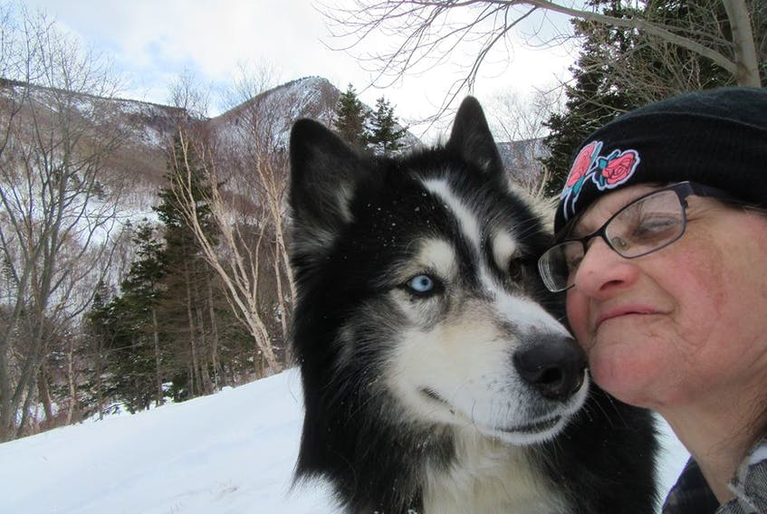 Arlene Fougere having an affectionate moment with her husky Cooper at home in Meat Cove. Fougere said it's frustrating as there still hasn't been a decision into a complaint she laid with the Nova Scotia Veterinary Medical Association after her dog was euthanized by mistake eight months ago. CONTRIBUTED