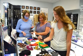 Sheila McCormick, left, manager of Emerald Isle on Welton Street in Sydney, shows customers Brenda Boutilier, centre, of Glace Bay, and her daughter Ashley Boutilier, an emergency room nurse in Halifax, some of their many non-medical reusable/washable face masks on hand. SHARON MONTGOMERY-DUPE/CAPE BRETON POST