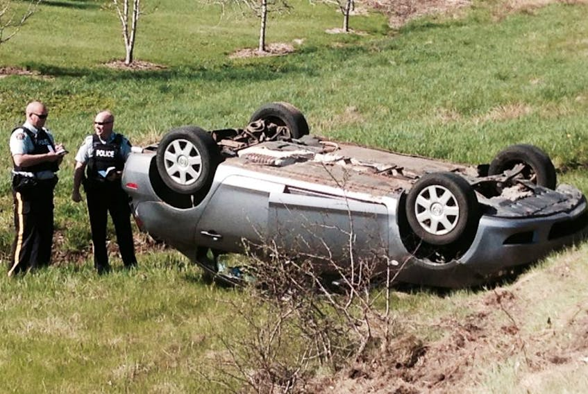 <p>RCMP Constables Danny O'Blenis and David McNulty examine a vehicle after it went off the road May 18.</p>