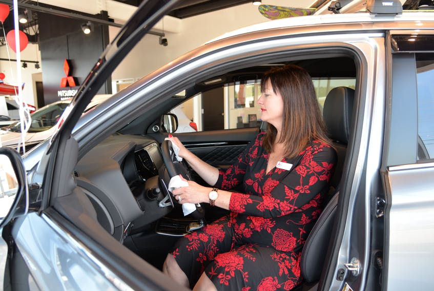 Tammy Roach, dealer principal and general manager of  Charlottetown Mitsubishi, sanitizes a vehicle in the showroom recently. She says sales in June so far have been fantastic.
