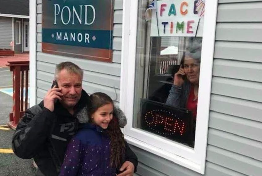 """Six-year-old Kenzie Rae and her Uncle Deano visited her nanny, Dora Poole, a resident of North Pond Manor in Torbay, last Friday through the home's """"FaceTime"""" window. Visitors are banned from entering long-term care residences during the COVID-19 pandemic. CONTRIBUTED PHOTO"""