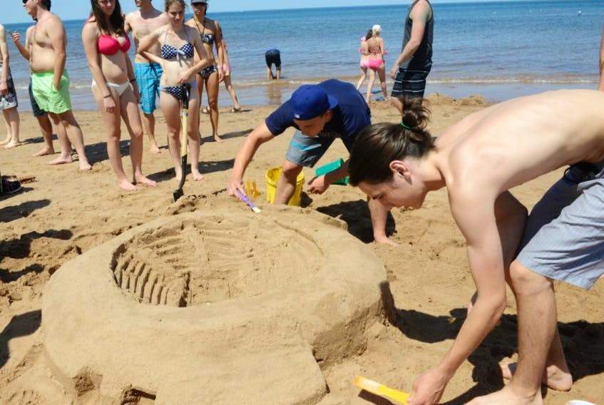 Philippe Cadorette, left, and Charles Desgagne put the finishing touches on a stadium-inspired sandcastle.