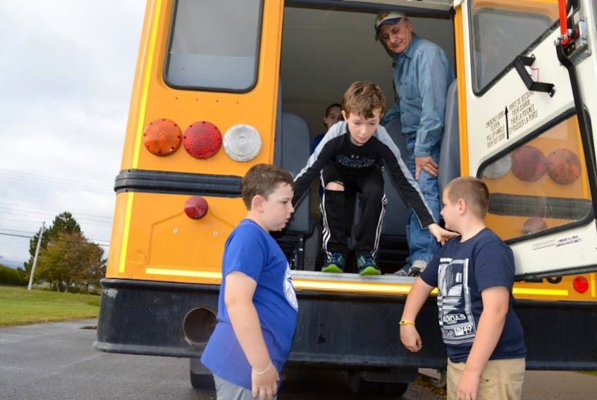 School bus drills take place every fall during Nova Scotia School Bus Safety Awareness Week. This file photo from last October shows Grade 5 student Alex Kennedy, centre, of New Waterford Elementary School, jumping off a school bus through the back emergency exit while being assisted by fellow Grade 5 students Keegan Stubbard, left, and Justin Spencer. Drivers are being reminded to watch for stopped school buses with the beginning of a new school year this week.