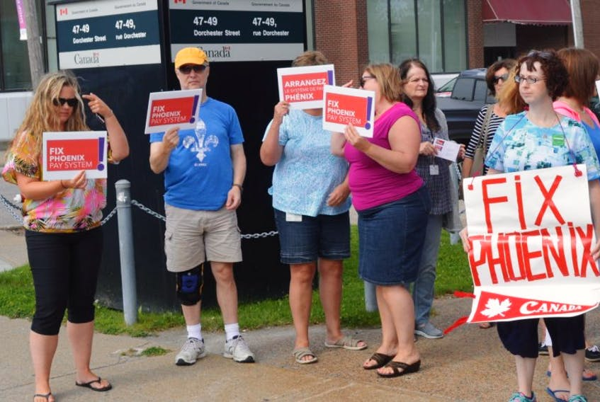 Dozens of people stand in front of the federal government building on Dorchester Street on Wednesday to protest the Phoenix Pay System.