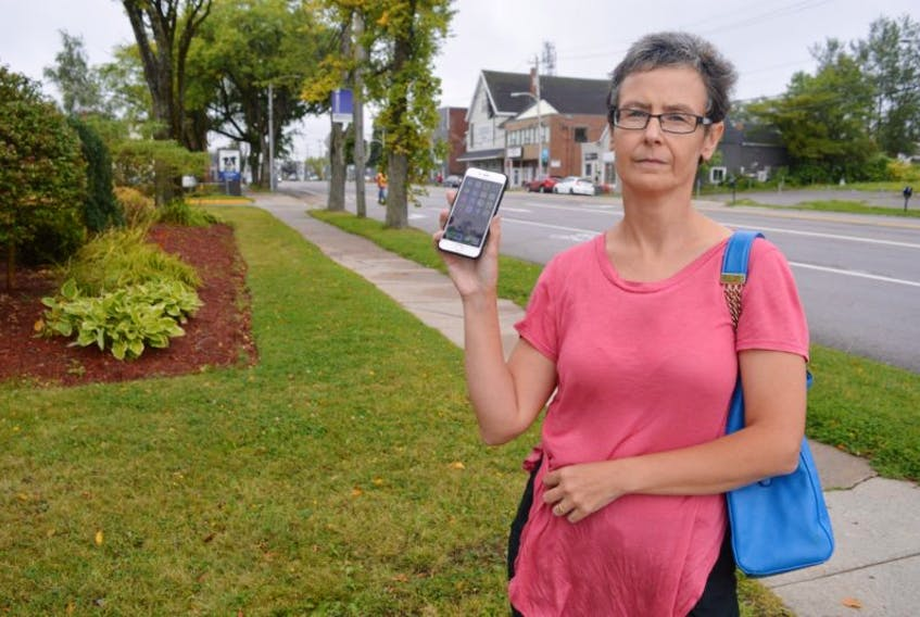 Sarah Morrison holds up her cell phone where she has saved text messages from Bell Aliant confirming they said they were waiting on a part to fix issues in the area and that she had informed them of 10 residences with no landline service.