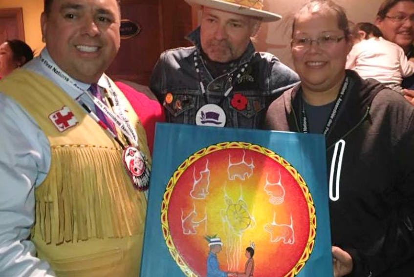 """Regional Chief Morley Googoo, left, and Loretta Gould, right, of Waycobah present Gord Downie, middle, with a special painting, entitled """"Share our Teachings,"""" at the Assembly of First Nations on Tuesday in Gatineau, Que. The painting was created by Gould for Downie."""
