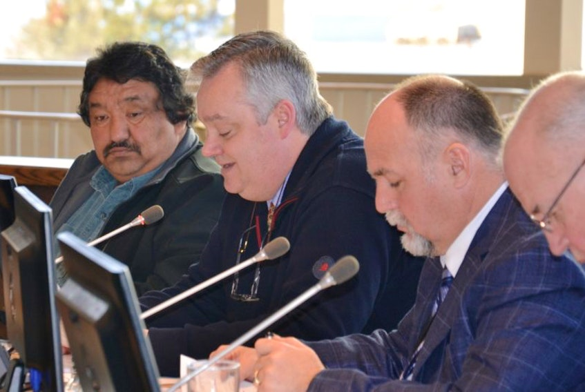 CBRM councillors Esmond Marshall, left, and Deputy Mayor Eldon MacDonald, at right, listen Tuesday as Steve Gillespie reads his motion to eliminate the $140 weekly allowance that members of council can currently claim.