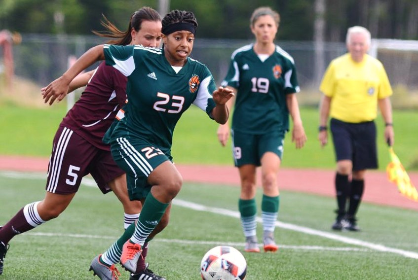 Cape Breton University striker Keona Simmonds head down the pitch while being pursued by Saint Mary's University defender Jani Marchand-Lemire during the Capers 6-0 season-opening win over the Huskies on Saturday at the CBU field. The Capers number 19, Becky Hanna, looks on.