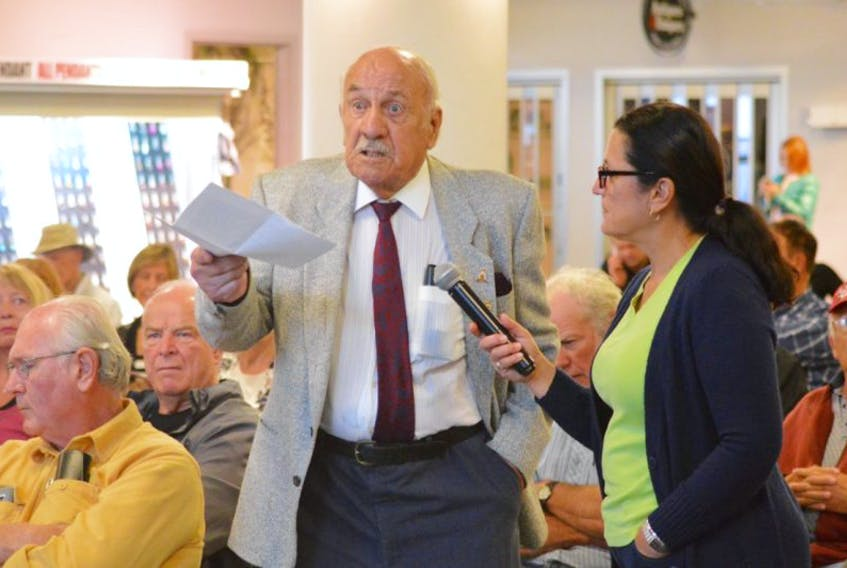 Ninety-five-year-old Charlie Palmer makes a point during his time on the microphone, held by Scotia Rail Development Society board member Patricia Morrison, during the organization's public meeting Sunday at the Joan Harriss Cruise Pavilion in Sydney.