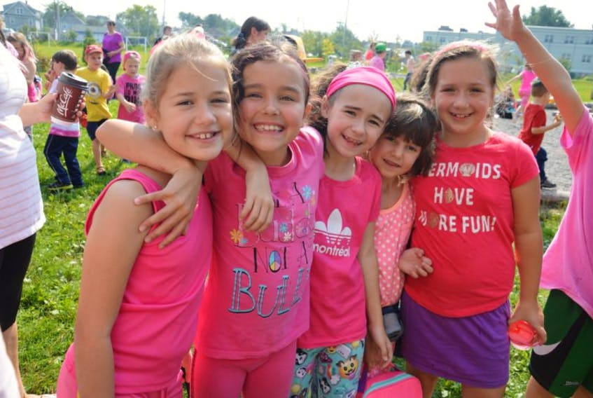 From left, Elin Laderoute, Davis Sullivan, Alivia Dolhanty, Emma Vatcher and Hannah Rudderham, all 8, share hugs and laughs during the Étoile de l'Acadie family barbecue for Anti-Bullying Day.