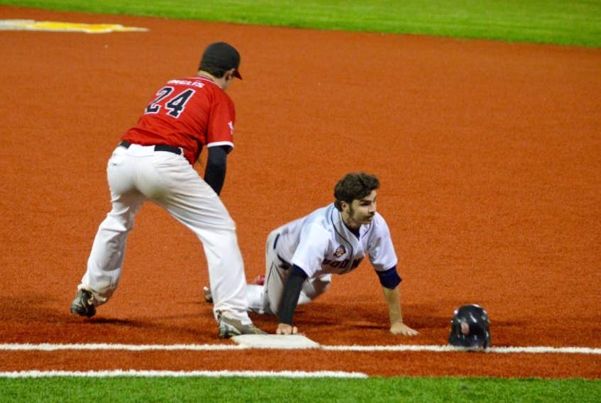 Mike Tobin, right, of the Sydney Sooners dives back to first base as Dan Bates of the Truro Bearcats slaps the tag on him during Nova Scotia Senior Baseball League playoff action at the Susan McEachern Memorial Ball on Friday. The Sooners won, 7-5.