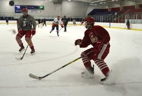 Jared Hunt, right, sprays some ice as he stops during a skating drill, alongside teammate Avery DeCoste, left, during practice at the County Recreation Centre in Coxheath on Tuesday. The two defencemen and other members of the Riverview Redmen were preparing for the first game in a new midget 'X' league sanctioned by Hockey Nova Scotia after the Cape Breton High School Hockey League was suspended because of the Nova Scotia teachers labour dispute. The work-to-rule job action by the Nova Scotia Teachers Union, which resulted in the cancellation of the Red Cup Showcase on Monday, has had a substantial impact on revenue at local rinks.