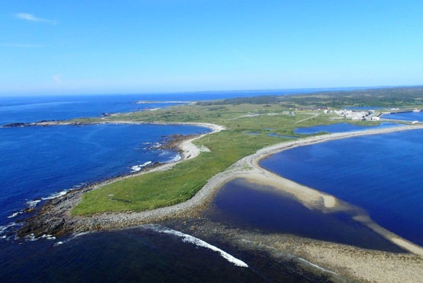 This aerial view shows Rochefort Point, in the foreground, with the reconstructed quarter of the Fortress of Louisbourg visible in the back right. The point is the site of a historic graveyard that is in jeopardy due to coastal erosion. Parks Canada is teaming with the University of New Brunswick's Department of Anthropology this summer to document, protect and preserve the 18th century burial ground.