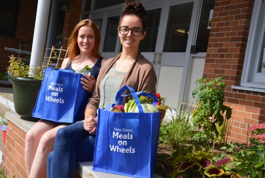 Claire Turpin, front, and Kathleen Whelan show off bags full of fresh produce and meat that will be delivered to seniors on Thursday as part of the age-friendly food box pilot program. The program is being done through meals on wheels and continues until Oct. 26.