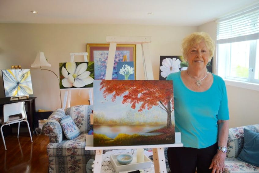 Cassie MacLeod stands by her artwork in the basement studio of her North Sydney home. MacLeod will be this year's featured artist at the Autumn Treasures Art Show, hosted by Rt. Hon. Vincent Massy Chapter IODE.