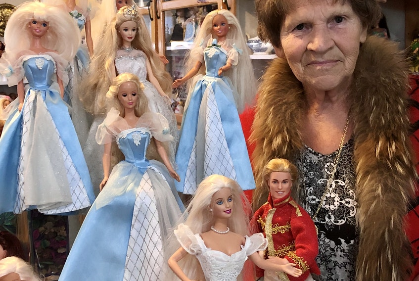 """Madonna Porter of C.B.S. poses with some of the Barbie dolls in her large collection — a collection that she is donating today to Branch 1 of the Royal Canadian Legion in St. John's. """"My dream is coming true,"""" Porter says of donating her collection to a worthy cause."""