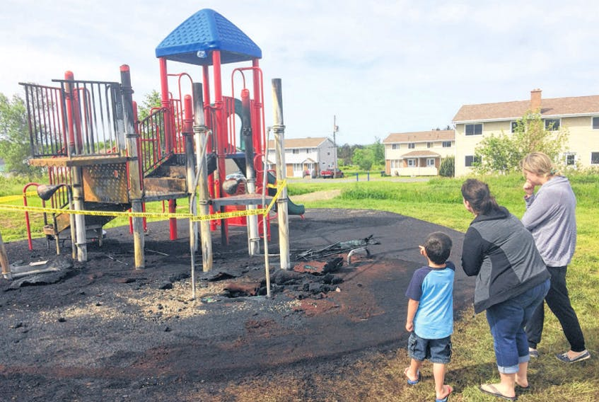 Charlene Spence and Gayle Snell and a neighbourhood child look over the damage from a fire in late June 2018. The Municipality of Cumberland announced it has awarded a $232,000 tender to ABC Recreation to build a new park on Mechanic Street to replace the one destroyed by fire. File