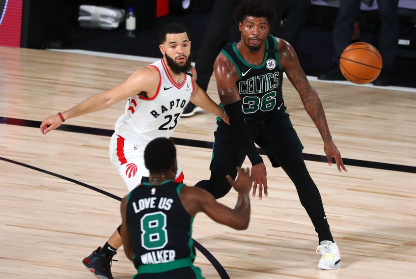 Boston Celtics guard Marcus Smart (36) passes the ball to guard Kemba Walker (8) as Toronto Raptors guard Fred VanVleet defends during the second quarter of Game 1 of their playoff series on Sunday.