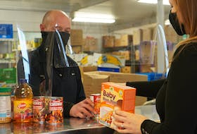 Worker Robert Gaudet serves a client at the Upper Room Hospitality Ministry food bank in Charlottetown.