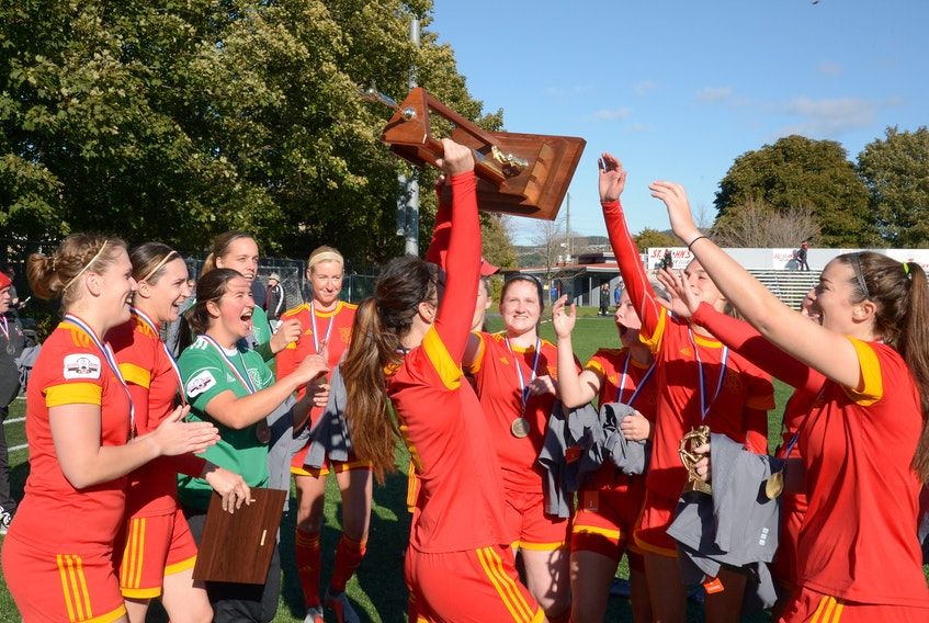 Holy Cross women's soccer team celebrate with the Breen's Jubilee Trophy championship hardware after beating Feildians 5-0 in the league final Monday at King George V Park. KEITH GOSSE/THE TELEGRAM