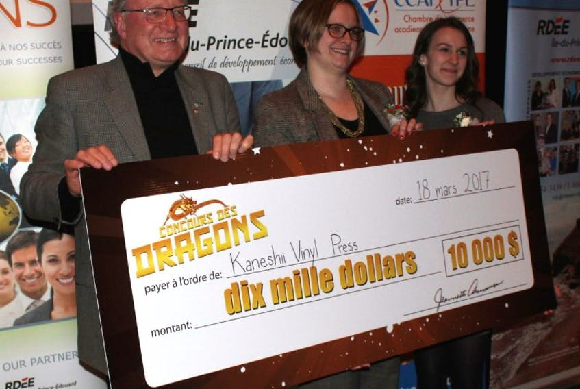 Premier Wade MacLauchlan helps Nicole Allain, right, coordinator of the 2017 Dragons' Contest, present the huge $10,000 cheque to champion Ghislaine Cormier of Charlottetown, who is setting up Kaneshii Vinyl Press.