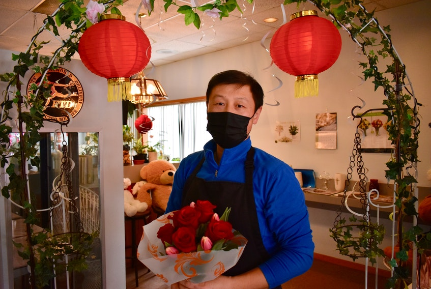 Larkin Lin, owner of Paul's Flower Shop on University Avenue in Charlottetown, holds a bouquet of roses in his store on Valentine's Day.