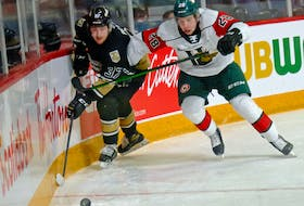 Charlottetown Islanders winger Bailey Peach, left and Halifax Mooseheads defenceman Stephen Davis battle for a loose puck during Sunday's Quebec Major Junior Hockey League contest in Halifax.