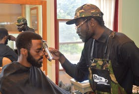 Luke Ignace, right, has opened a barbershop on Victoria Row in Charlottetown that aims to create conversation and opportunities among the Black community but is open to everyone. Here he gives his friend, Loki, a trim.