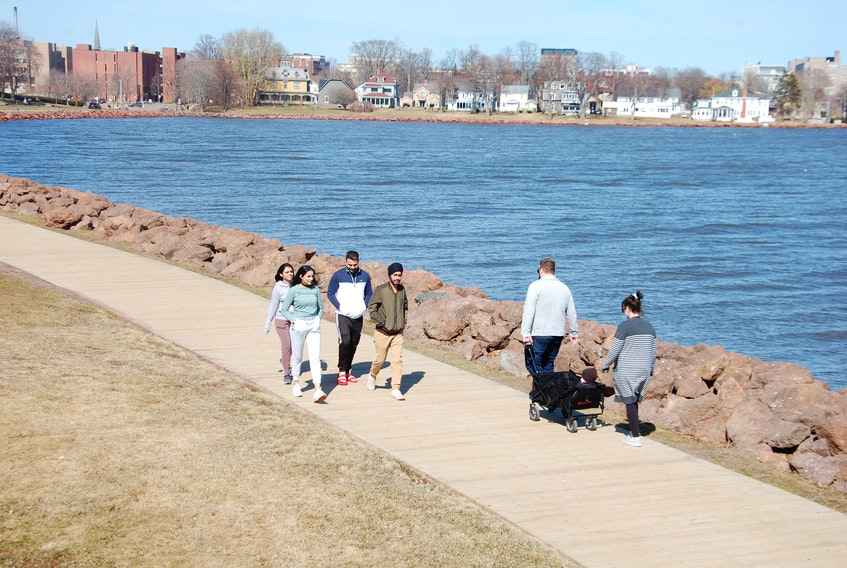 Pedestrians enjoy a stroll on the boardwalk around Victoria Park in Charlottetown on a recent warm, sunny afternoon.