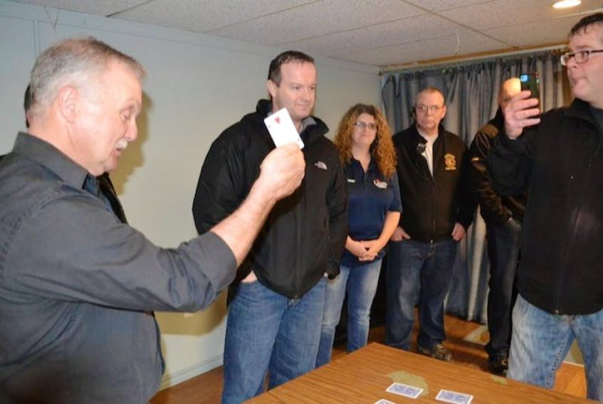 Wade Smith, centre, gives little reaction as Tignish Legion member holds up the deuce of hearts, indicating he hadn't won the jackpot in Tignish's wildly popular Chase the Ace lottery. The jackpot now stands at $597,729.