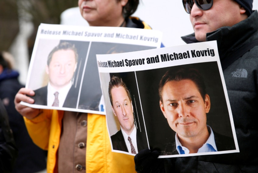 People hold signs calling for China to release Canadian detainees Michael Spavor and Michael Kovrig during an extradition hearing for Huawei Technologies Chief Financial Officer Meng Wanzhou at the B.C. Supreme Court in Vancouver, in March 2019.