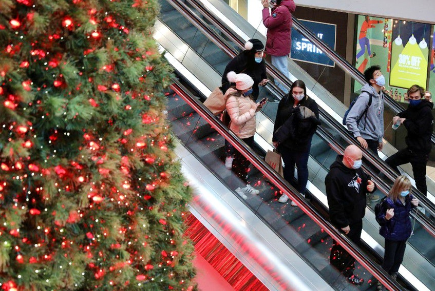 Shoppers wearing mandatory masks pass Christmas Tree, two days before coronavirus disease (COVID-19) restrictions are reintroduced to Greater Toronto Area regions, at Eaton Centre mall in downtown Toronto, Ontario, Canada November 21, 2020.