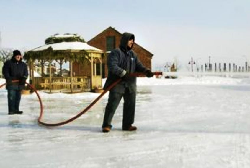 ['In this Guardian file photo, Charlottetown parks and recreation worker Ken Flanagan holds the hose steady for Todd Steele as he floods the rink near Founders Hall.']