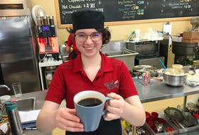 Haley Bishop of Kate's Bakery in New Minas holds a ceramic mug of coffee Tuesday. Like other small shops, Kate's is still using the mugs and filling reusable mugs for customers.