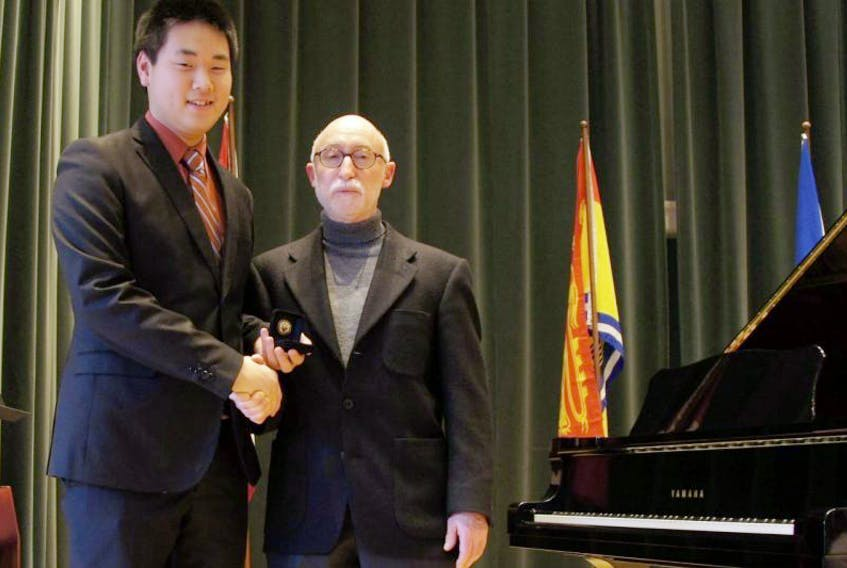 <p>Colin Yee receives a gold medal for obtaining the highest mark in the Atlantic Region on his&nbsp;Grade 10&nbsp;Piano exam from Dr. Thomas Green of The Royal Conservatory. (contributed photo)</p>
