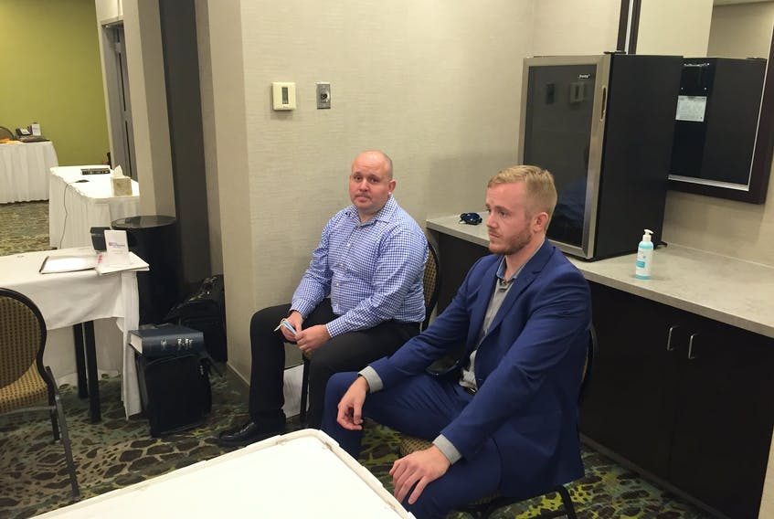 Kenneth O'Brien, left, and Brent Woodworth, constables with Halifax Regional Police, get ready to listen to testimony Thursday, Oct. 8, during a hearing to address a complaint filed against them by Adam LeRue and Kerry Morris of racial profiling and unwarranted arrest dating back to a Feb. 12, 2018. The complaint is being heard by a three-member Police Review Board at the Hilton Garden Inn near the Halifax airport.