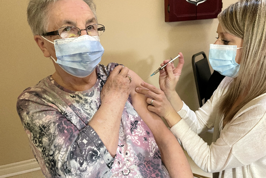 Emma Miller, a resident of Mountain View Retirement Centre in Corner Brook, is injected with the first dose of a COVID-19 vaccine by public health nurse Joy Green.
