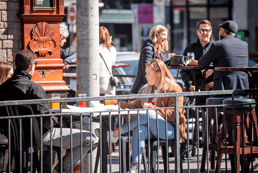 People sit at a restaurant patio to take advantage of sunny weather in Ottawa, March 20, 2021.