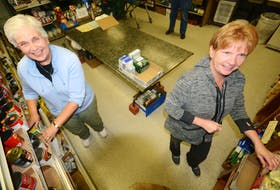 Charlotte Ross, left, and Christine Davis restocked shelves at the Amherst Food Bank. COVID-19 has changed the way people pick up and drop food off at the food bank. File Photo