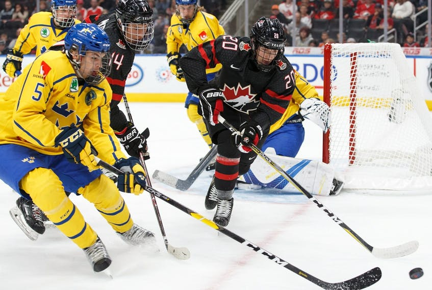 Canada's Dylan Holloway (20) battles Sweden's Alexander Lundqvist (5) for puck possession during the Hlinka-Gretzky Cup gold medal game in Edmonton on August 11, 2018.