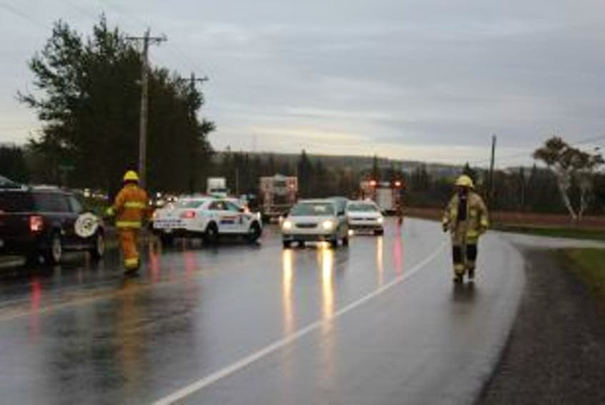 ['Fire crews direct traffic at the scene of a Sunday afternoon crash on the Trans Canada Highway.']