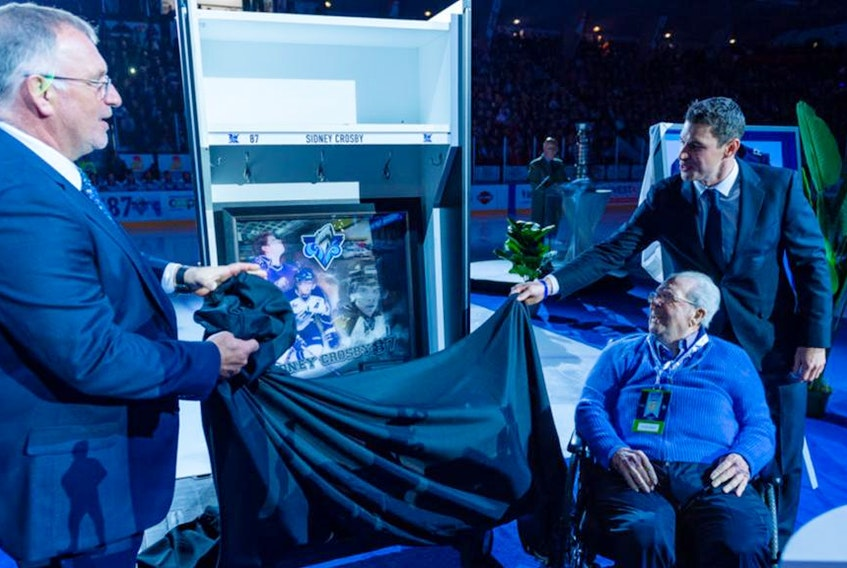 Sidney Crosby, right, and Maurice Tanguay, seated, celebrate the retirement of Crosby's No. 87 Rimouski Oceanic jersey during a 2019 ceremony in Rimouski, Que.