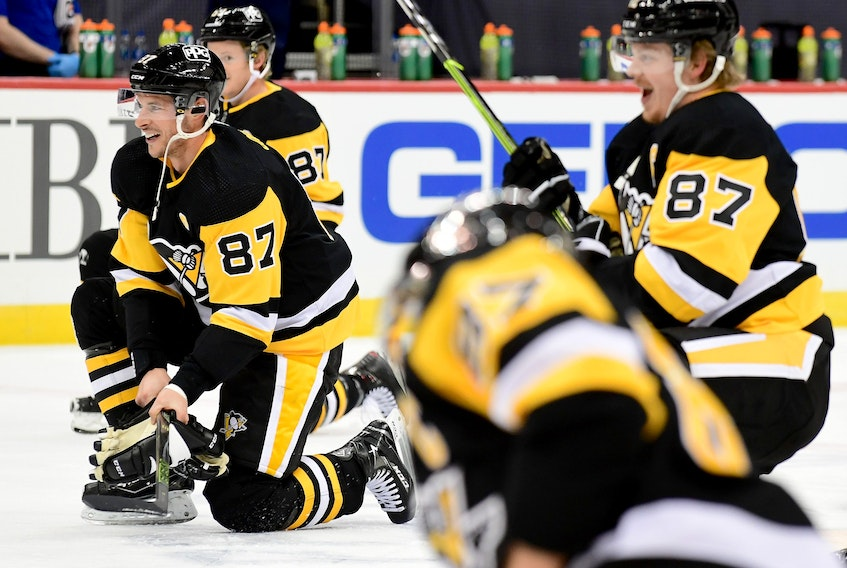 Penguins players take a knee and imitate Sidney Crosby's pre-game ritual of untying a skate and tying it back up to celebrate his 1,00th NHL game on Saturday.