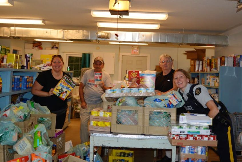 <p>Michelle Parker (Kings County Senior Safety), Upper Room Food Bank volunteers Roger Penny and Harley Hazelwood and Kings District RCMP Const. Kelli Gaudet gather around donations collected during a recent Cram the Cruiser event held in support of the food bank.</p>