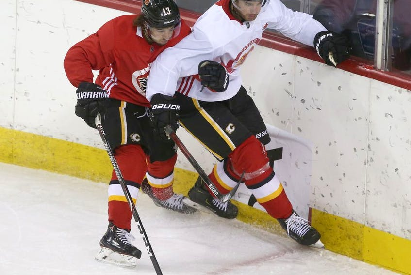 Johnny Gaudreau and Noah Hanifin collide along the boards during Calgary Flames training camp at the Saddledome in Calgary on July 14, 2020. Jim Wells/Postmedia