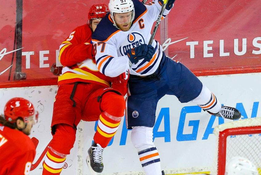 Calgary Flames' Noah Hanifin collides with Connor McDavid of the Edmonton Oilers in Calgary on March 15, 2021.