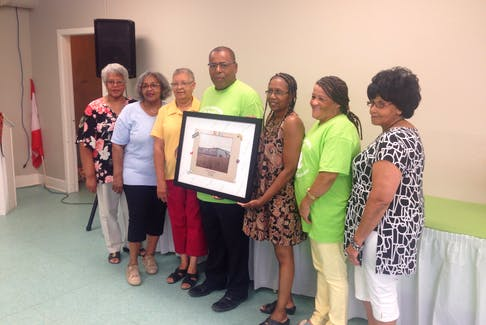 A committee of volunteers from the Wallace Lucas Community Centre are pictured with a piece of artwork that includes the names of all the teachers who worked at the former school.