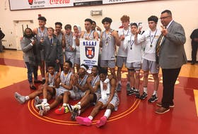 Members of the Dartmouth Spartans pose with their banner after beating the Halifax Grammar School Gryphons in the provincial boys' basketball championship game at the Homburg Centre. (WILLY PALOV/Chronicle Herald)